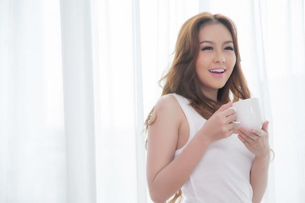 Schöne asiatische frauen, die kaffee mit raum trinken