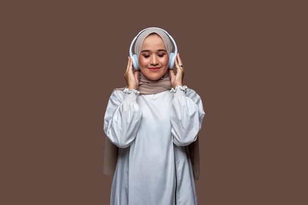 Schöne asiatische frauen im hijab, die drahtlose kopfhörer tragen, während sie ihre augen schließen
