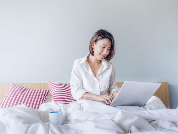 Schöne asiatische frauen mit kurzen haaren tragen weißes hemd, das mit laptop-computer auf dem bett im haus arbeitet.
