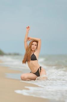 Schöne asiatische frauen oder thailändische frauen und schwarze bikinis am strand, die am strand für das reisen im sommerkonzept entspannen
