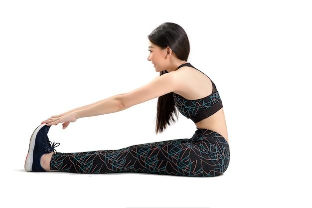 Schöne asiatische frauen wärmen sich auf, bevor sie sport und yoga machen. foto des asiatischen mädchens durch lokalisierten weißen hintergrund. fitness- und gesundes lifestyle-konzept.