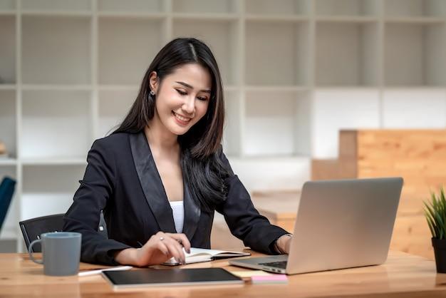 Schöne asiatische geschäftsfrau arbeitet mit einem tablet und einem laptop mit dokumenten im büro.