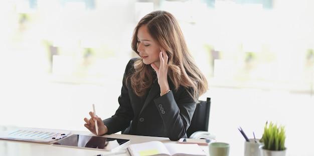 Schöne asiatische geschäftsfrau, die an ihrem projekt beim schreiben auf tablette arbeitet