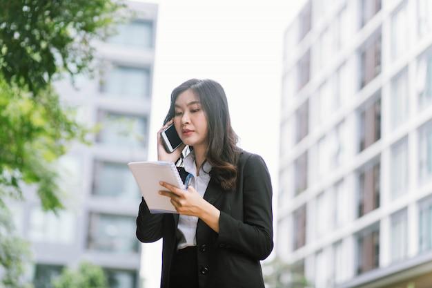 Schöne asiatische geschäftsfrau, die auf einem handy spricht, während sie im freien geht
