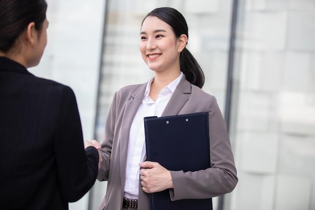 Schöne asiatische geschäftsfrau, die hände im modernen stadtarbeitsbüro schüttelt.