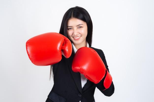 Schöne asiatische geschäftsfrau, die in der hand einen boxhandschuh und einen anzug trägt
