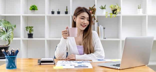 Schöne asiatische geschäftsfrau, die in ihrem privaten büro sitzt, kaffee trinkt und sich informationen auf ihrem laptop ansieht, sie ist die weibliche führungskraft eines startup-unternehmens. konzept des finanzmanagements