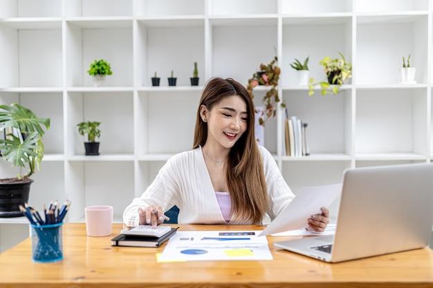 Schöne asiatische geschäftsfrau, die in ihrem privaten büro sitzt, mit ihrem partner über laptop chattet und dokumente überprüft, sie ist eine weibliche führungskraft eines startup-unternehmens. finanzmanagementkonzept.