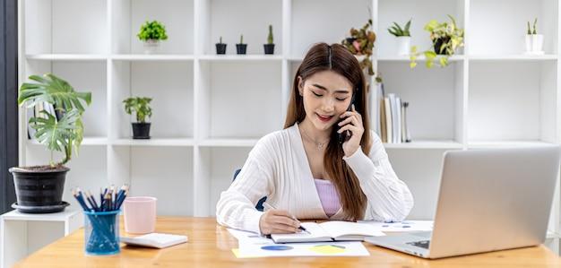 Schöne asiatische geschäftsfrau, die in ihrem zimmer sitzt, mit ihrem partner über das handy spricht und finanzdokumente überprüft, sie ist eine weibliche führungskraft eines startup-unternehmens. finanzverwaltung.