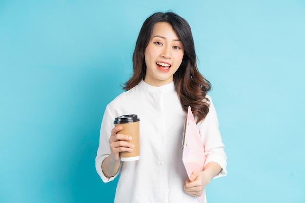 Schöne asiatische geschäftsfrau, die papierkaffeetasse und broschüre in der hand hält