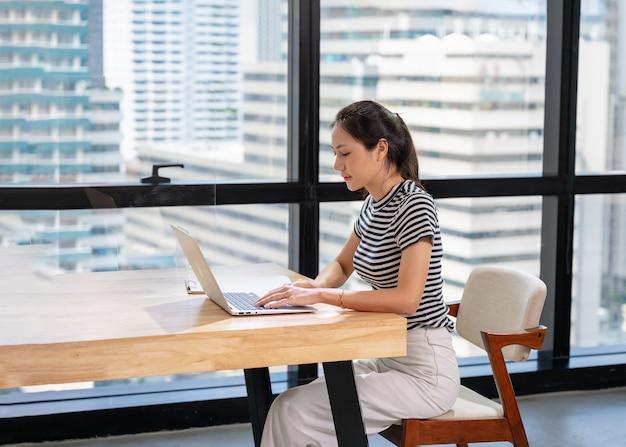 Schöne asiatische geschäftsfrau im lässigen stoff, der mit dem schreiben auf laptop am schreibtisch im modernen büro durch fenster arbeitet