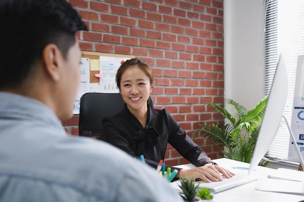 Schöne asiatische geschäftsfrau interviewt männliche bewerber im amt.