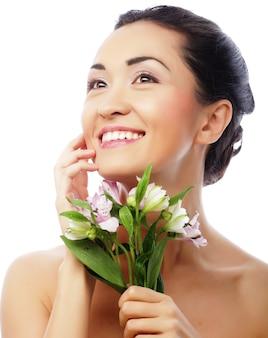 Schöne asiatische glückliche frau mit rosa blumen, lokalisiert auf weiß