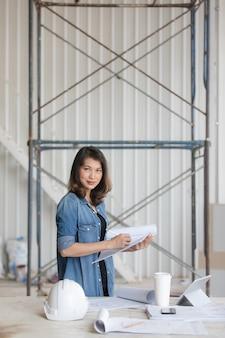 Schöne asiatische ingenieurfrau in der blue jeanshemdstellung und -schreiben