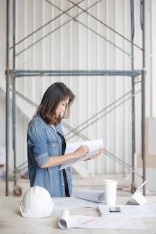 Schöne asiatische ingenieurin in blauem jeanshemd, die weißen sicherheitshelm auf schreibtisch steht und schreibt