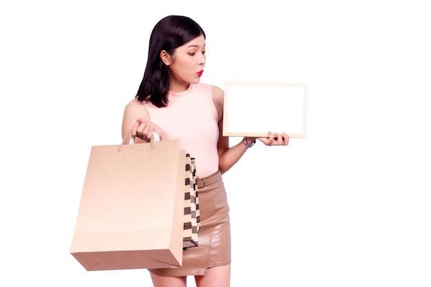 Schöne asiatische intelligente frau, die einkaufstaschen trägt und das leere hölzerne weiße brett, lokalisiert, nahes hohes hält. das porträt der asiatin lokalisiert auf weißer szene. shopaholic-konzept.
