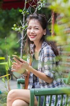 Schöne asiatische jüngere frau, die mit dem glückgefühl liest intelligentes telefon lacht