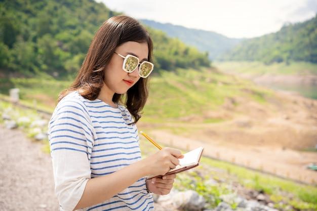 Schöne asiatische junge frau, die eine notiz in ihr notizbuch nimmt. konzept der weiblichen reisenden.