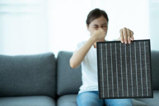 Schöne asiatische junge frau, die einen hepa-kohlenstoff-luftreinigerfilter im wohnzimmer hält, frau bereitet einen luftreinigerfilter vor, um den alten zu ersetzen. gesundheitswesen und gutes lebensstilkonzept.