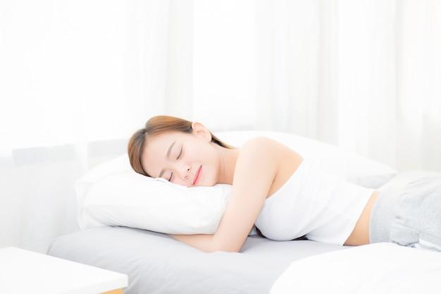 Schöne asiatische junge frau, die im bett mit kopf auf kissen liegend schläft.