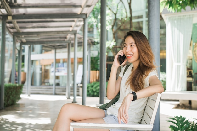 Schöne asiatische junge frau, die smartphone für die unterhaltung verwendet