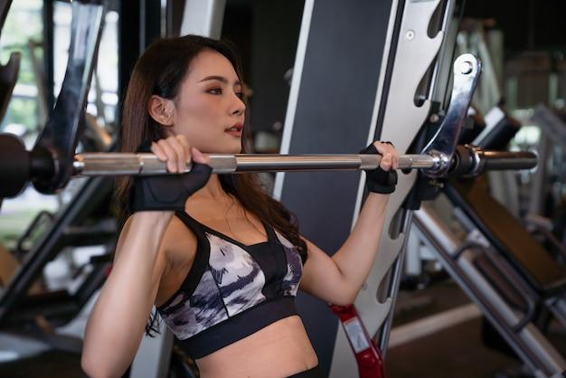 Schöne asiatische junge frau, die training und übung mit dem heben von hanteln am fitness-sport-sportverein trainiert