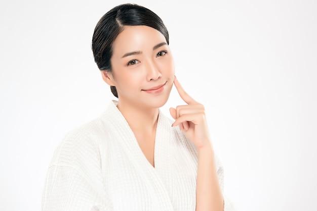 Schöne asiatische junge frau, die weiche backe und lächeln mit sauberer und frischer haut berührt. glück und fröhlich mit, isoliert auf weiss, schönheit und kosmetik,