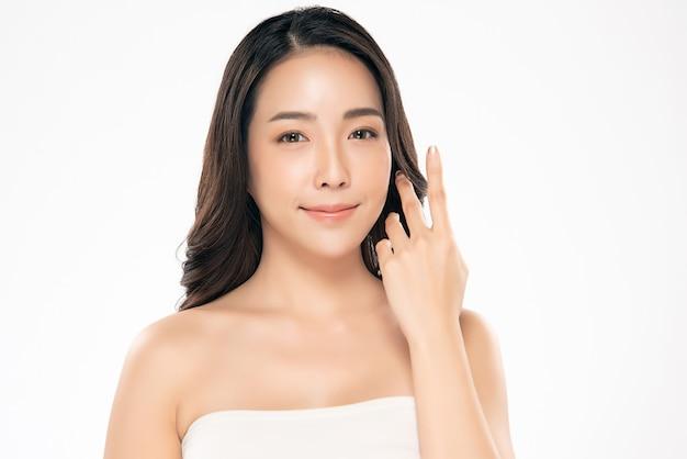 Schöne asiatische junge frau, die weiches backenlächeln mit sauberem und neuem haut glück berührt