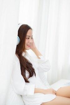Schöne asiatische junge frau genießen hören musik mit kopfhörer.