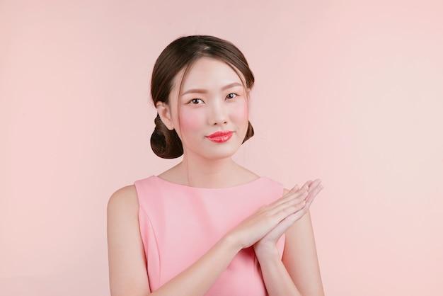 Schöne asiatische junge frau mit dem mode-make-up lokalisiert auf rosa. kosmetik und make-up