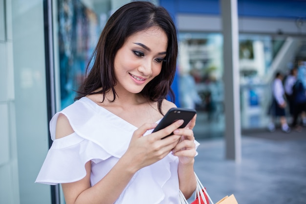 Schöne asiatische junge frau mit einkaufstaschen unter verwendung ihres smartphones mit lächeln beim stehen am bekleidungsgeschäft. glück, konsum, verkauf und menschenkonzept