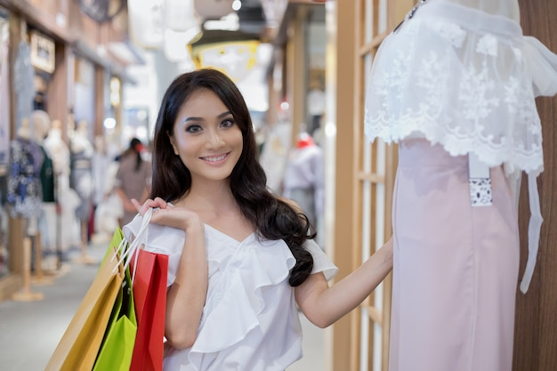 Schöne asiatische junge frau mit einkaufstüten mit lächeln beim stehen im bekleidungsgeschäft. glück, konsum, verkauf und menschenkonzept