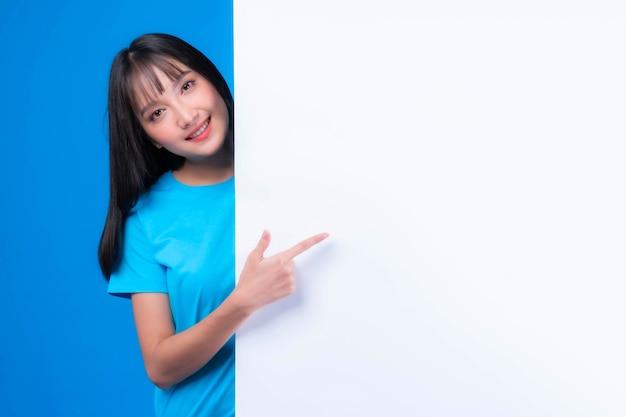 Schöne asiatische junge frau mit ponyfrisur im blauen t-shirt, die lächelt und mit dem finger auf eine leerstelle für werbebanner zeigt, leeres weißes brett ein leeres banner einzeln auf blauem hintergrund