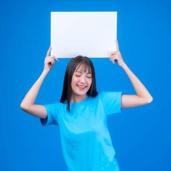 Schöne asiatische junge frau mit ponyfrisur in blauem t-shirt lächelt und hält einen leeren platz für werbebanner, weißes brett ein leeres banner isoliert auf blauem hintergrund