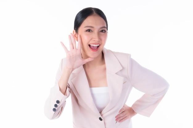 Schöne asiatische junge frau schreit die gute nachricht oder promotion an und hält die hände in der nähe ihres gesichts mit offenem mund herald news promotion isoliert auf weißem hintergrund