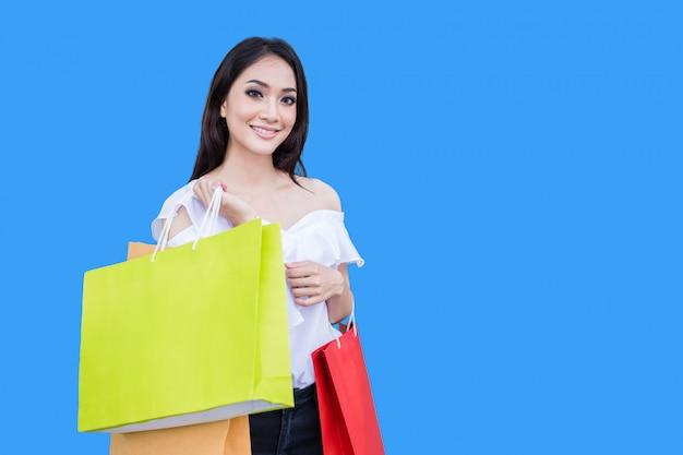 Schöne asiatische junge frau steht und hält einkaufstaschen. sie lächelt glück im einkaufszentrum auf blauem hintergrund
