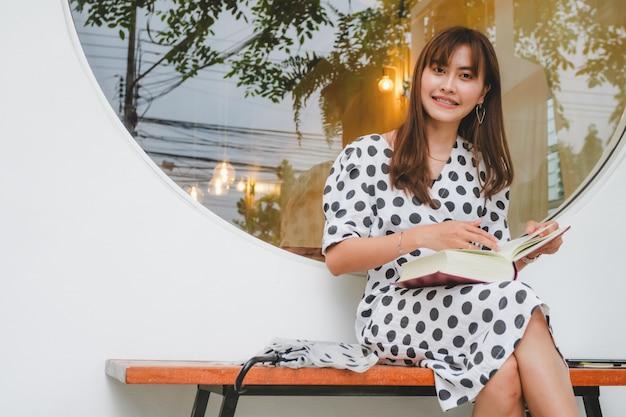 Schöne asiatische junge frauen, die das lesebuch im freien sitzen