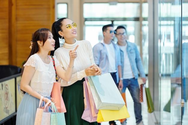 Schöne asiatische junge frauen mit vielen einkaufstüten verbringen das wochenende im kaufhaus