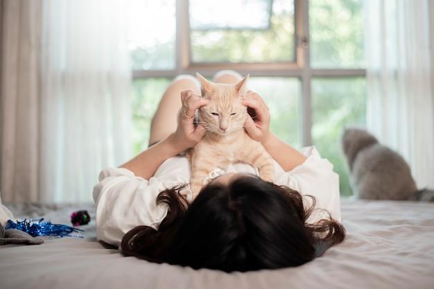 Schöne asiatische katzenliebhaberfrau spielt mit katze in ihrem zimmer