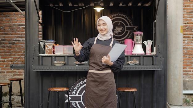Schöne asiatische kellnerin bringt eine menüliste und gestikuliert im café-standcontainer?