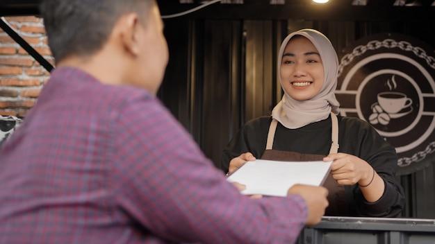 Schöne asiatische kellnerin, die den kunden am ankringan-containerstand eine menüliste gibt