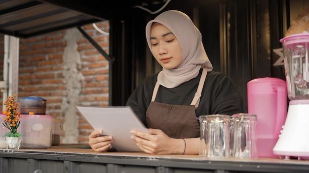 Schöne asiatische kellnerin, die die menüliste ernsthaft im café-standcontainer liest?