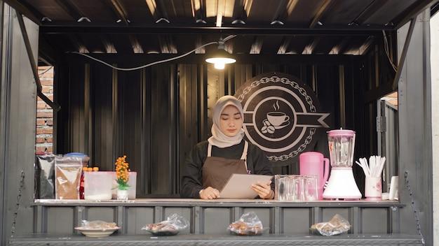 Schöne asiatische kellnerin, die die menüliste im café-standcontainer liest?