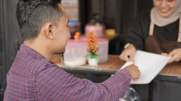 Schöne asiatische kellnerin, die kunden bedient, die am ankringan-containerstand bestellt haben?
