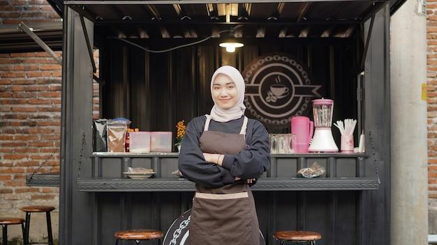 Schöne asiatische kellnerin mit servierfertigen armen am café-standcontainer