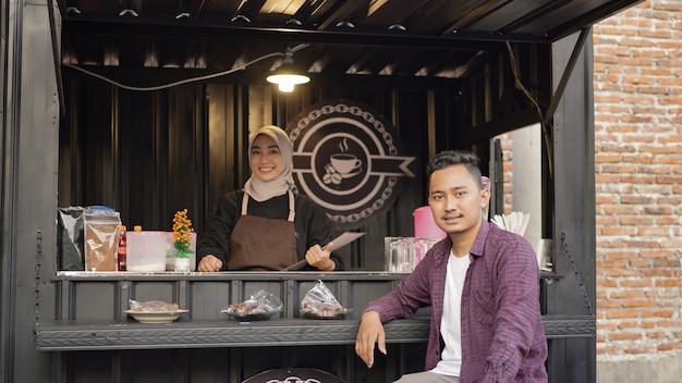 Schöne asiatische kellnerin und lächelnde kunden in beiden container-angkringan