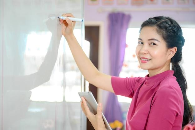 Schöne asiatische lehrerin, die auf der weißen tafel schreibt, die schüler in der schule im klassenzimmer für bildung unterrichtet