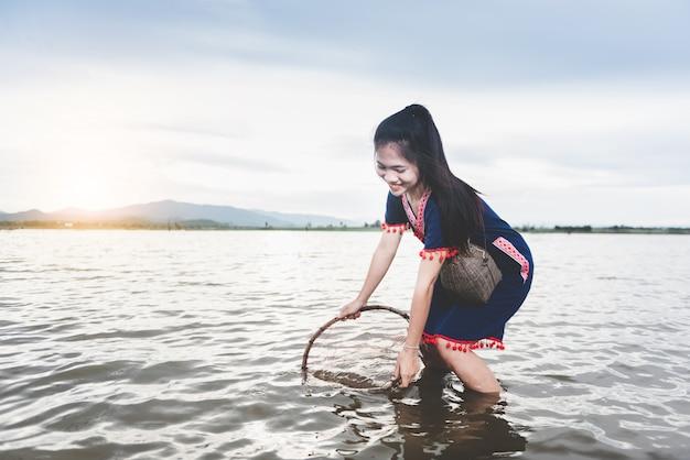 Schöne asiatische mädchen, die im see mit fischfalle fischen. lebensstil von leuten in der landschaft von thailand