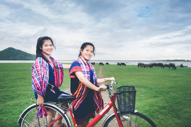 Schöne asiatische mädchen genießen reise an der landschaft von thailand, indem sie auf fahrrad fahren