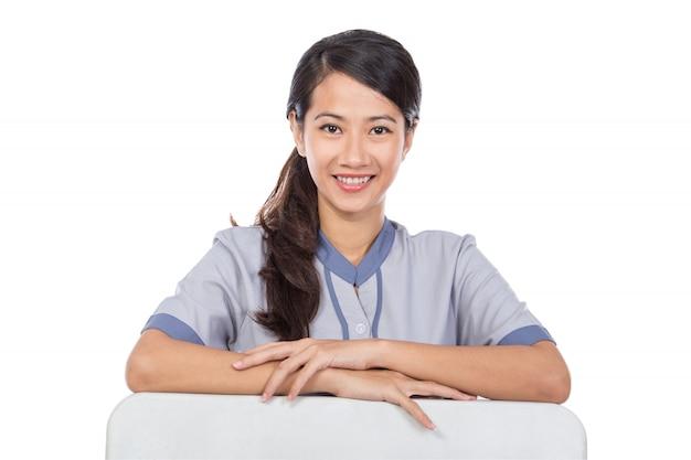 Schöne asiatische magd in uniform mit weißer tafel